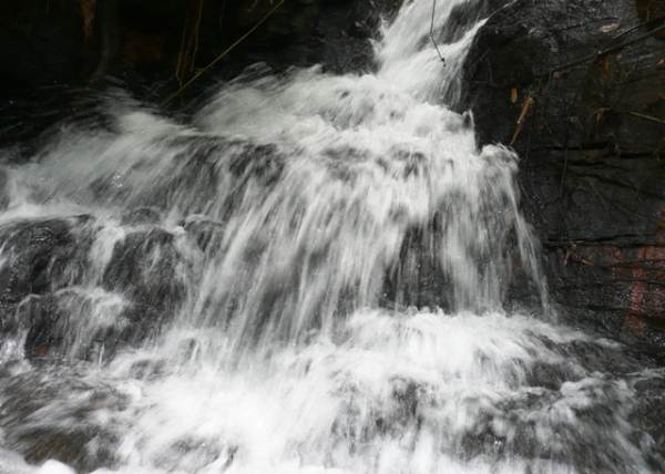 A cascade at the left edge of the rocky wall