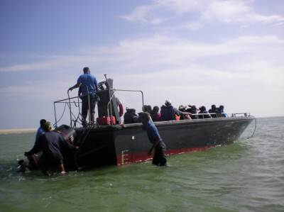 The rest of the crew arriving in a larger boat