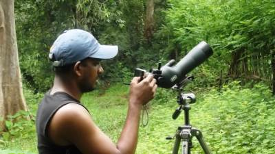 My friend taking photographs of bird though Digi-scoping equipments