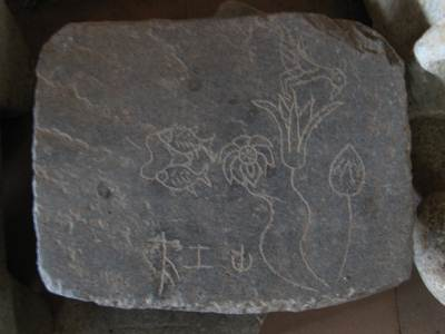 A stone with an expression of 'Anithya'. Two fish resembles the endless voyage through sansara. Flower bud resembles the infant stage, flower which bird sucking nectar resembles young adult and the other flower resembles the elderly stage