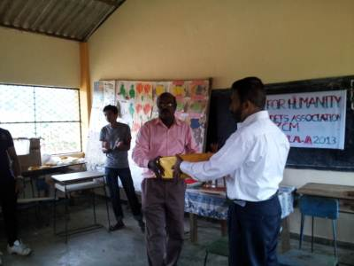 Lt. Ziyard is presenting office stationeries to Mr.Mahendran