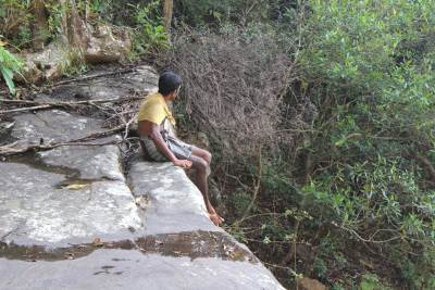 Our guide Jayantha relaxing on top of 3rd waterfall according to Malaka's map.